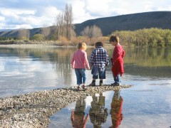 Clarks Reach in Pisa Moorings, kids on the shore of Lake Dunstan